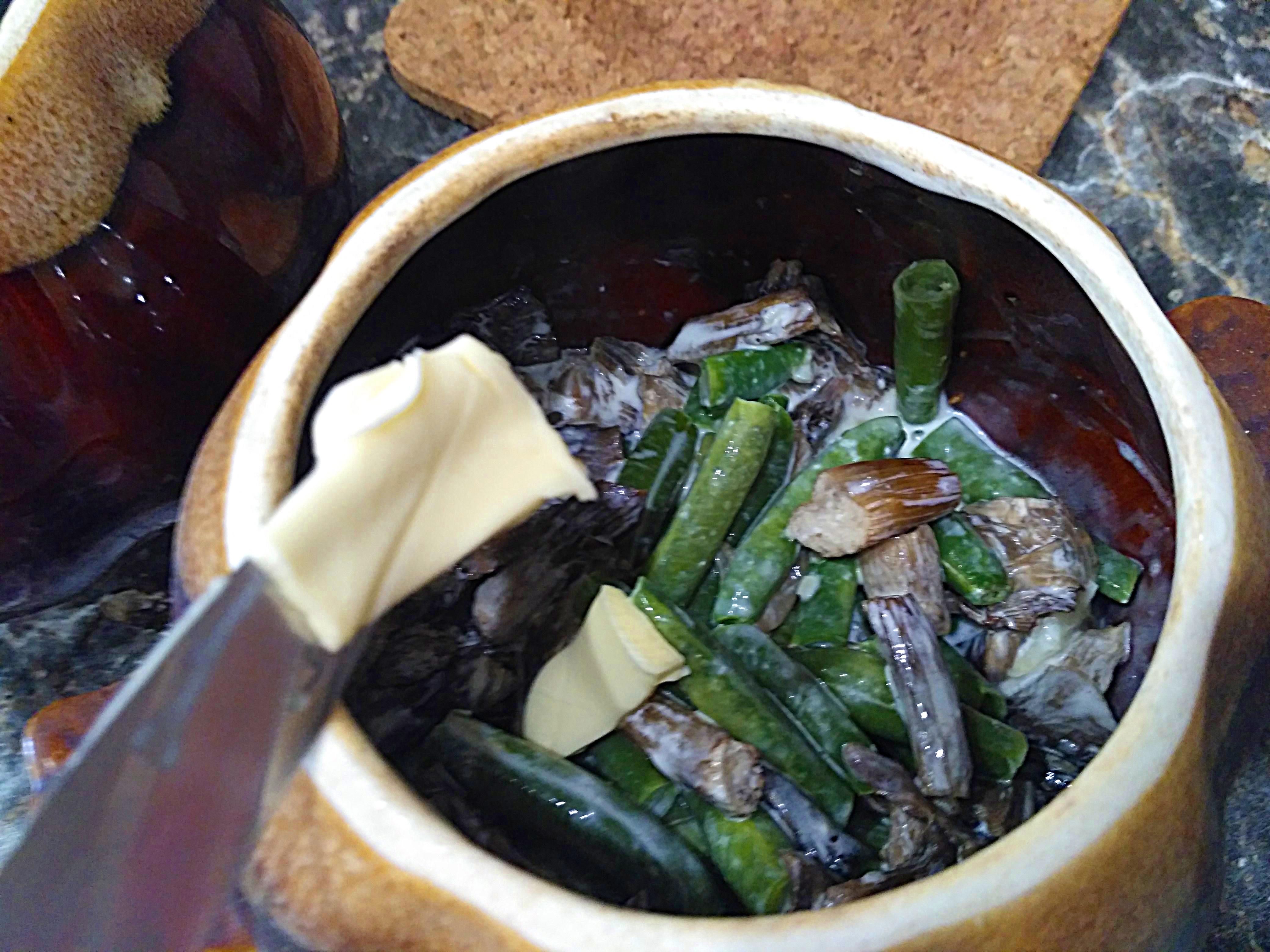 кладем сливочное масло в горшочек с грибами и фасолью