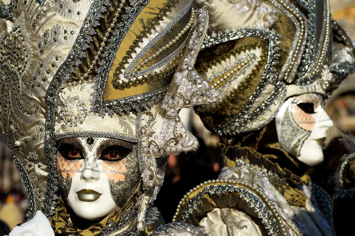 участники венецианского карнавала в костюмах и масках