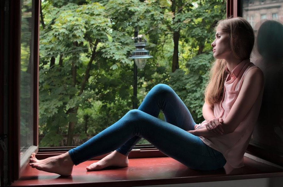 Девушка грустит у окна. Жить без доверия с любимым мужчиной сложно.